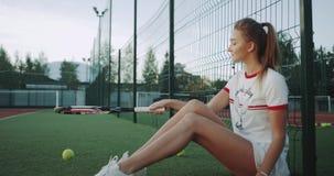Pallina da tennis con femmina del primo piano uno della racchetta una bella, seduta di battitura giù nell'erba al campo da tennis archivi video