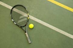 Pallina da tennis con la racchetta sulla corte wallpaper Fotografia Stock