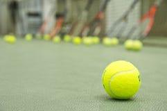 Pallina da tennis con le racchette e rete ai precedenti wallpaper Fotografia Stock