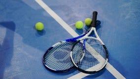 Pallina da tennis e racchetta su una corte blu con stanza per la copia video d archivio