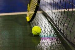 Pallina da tennis, racchetta e rete su terra bagnata dopo la pioggia Fotografie Stock