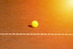 Pallina da tennis sui precedenti arancio e netti della corte per progettazione Fotografia Stock