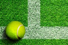 Pallina da tennis sul campo da tennis sull'erba con lo spazio della copia Fotografie Stock Libere da Diritti