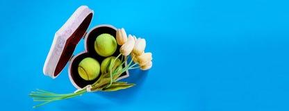 Palline da tennis della disposizione di amore di tennis in scatola nella forma di cuore con i tulipani bianchi del mazzo su fondo fotografie stock libere da diritti
