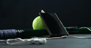 Palline da tennis, racchetta e telefono cellulare con le cuffie in studio 4k archivi video