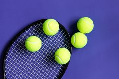 Palline da tennis sulla racchetta nera Fondo viola Sport di concetto Fotografie Stock Libere da Diritti