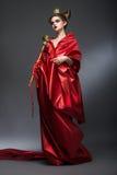 中古。魔术。红色Pallium的高傲的妇女巫术师与君权。巫术 库存照片