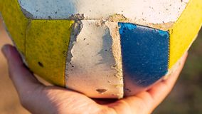 Pallone da calcio bianco, giallo e blu che riposa su una mano durante l'ora dorata fotografia stock