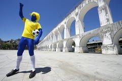 Pallone da calcio brasiliano blu Rio della tenuta del giocatore di football americano Fotografie Stock