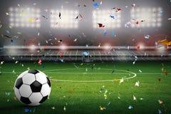 Pallone da calcio con stadio di calcio ed il fondo dei coriandoli Immagini Stock Libere da Diritti