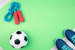 Pallone da calcio e corda di salto sulla stuoia verde immagini stock libere da diritti
