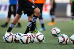 Pallone da calcio e piedi dei giocatori Fotografia Stock Libera da Diritti