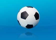 Pallone da calcio sopra il blu Fotografie Stock Libere da Diritti