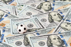 Pallone da calcio sopra molti soldi Fotografie Stock