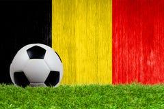 Pallone da calcio su erba con il fondo della bandiera del Belgio Fotografie Stock Libere da Diritti