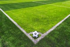Pallone da calcio su erba luminosa e verde scuro artificiale a pubblico Immagine Stock