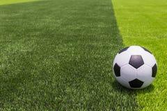 Pallone da calcio su erba luminosa e verde scuro artificiale a pubblico Fotografie Stock Libere da Diritti