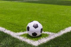 Pallone da calcio su erba luminosa e verde scuro artificiale a pubblico Fotografie Stock