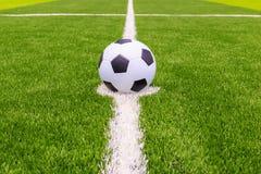 Pallone da calcio su erba luminosa e verde scuro artificiale a pubblico Fotografia Stock