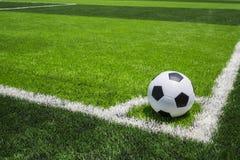 Pallone da calcio su erba luminosa e verde scuro artificiale a pubblico Immagini Stock Libere da Diritti