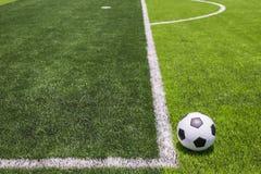 Pallone da calcio su erba luminosa e verde scuro artificiale a pubblico Immagini Stock