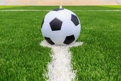 Pallone da calcio su erba luminosa e verde scuro artificiale a pubblico Fotografia Stock Libera da Diritti