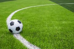 Pallone da calcio su erba luminosa e verde scuro artificiale a pubblico Immagine Stock Libera da Diritti