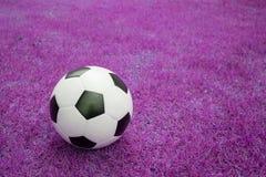Pallone da calcio su erba rosa fotografie stock