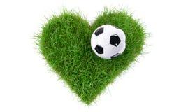 Pallone da calcio sull'erba di forma del cuore immagine stock libera da diritti
