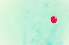 Pallone rosso sopra un retro cielo Fotografia Stock