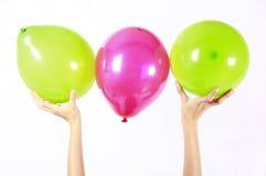 Pallone verde e rosa sostenuto in aria in studio fotografia stock libera da diritti