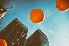 Palloni arancio con le costruzioni corporative nei precedenti Fotografia Stock
