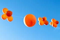 Palloni arancio contro un cielo blu Fotografia Stock
