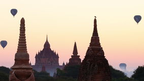 Palloni che sorvolano la siluetta antica del tempio buddista a Bagan Myanmar (Birmania) archivi video