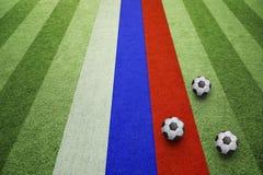 Palloni da calcio e bandiera della Russia sul campo Fotografia Stock