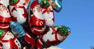 Palloni di Natale dell'elio delle forme differenti e dei caratteri che galleggiano nel cielo blu stock footage