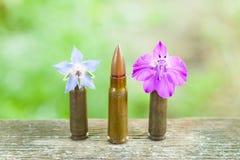 Pallottola che maschera fra i fiori Fotografia Stock