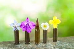 Pallottola che maschera fra i fiori Fotografie Stock Libere da Diritti