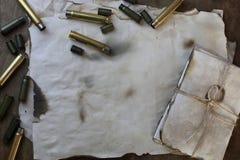 Pallottola e retro carta sulla tavola immagini stock