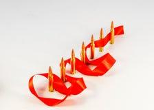 Pallottole del fucile Manica d'ottone Con un nastro rosso su un backg bianco Fotografie Stock