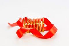 Pallottole del fucile Manica d'ottone Con un nastro rosso su un backg bianco Fotografia Stock