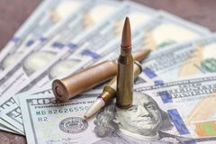 Pallottole dell'arma sul fondo americano dei dollari Industria militare, guerra, commercio di armi globale e concetto di crimine fotografia stock libera da diritti