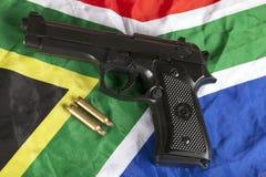 Pallottole dell'ottone e della rivoltella su una bandiera sudafricana Fotografia Stock Libera da Diritti