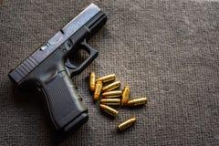 Pallottole e pistola di 9mm sullo scrittorio nero del velluto fotografia stock libera da diritti