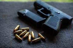 Pallottole e pistola sullo scrittorio nero del velluto fotografia stock libera da diritti