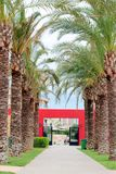 Palm alley and red gate Stock Photo