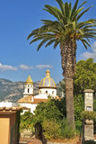 Palm at Amalfi. A church and villa in the Amalfi coast with Positano in the background Stock Image