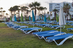 Palm Beach méditerranéenne avec des lits pliants vides au coucher du soleil photo libre de droits