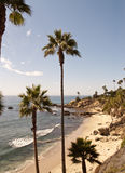 Palm beach with rocks. Shot of a sand beach scene with palmtrees and  small rocks in the water. California, USA Royalty Free Stock Images