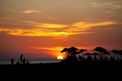 Palm beach umbrella at sunset. Beautiful beach silhouettes of palm beach umbrella at sunset Royalty Free Stock Image